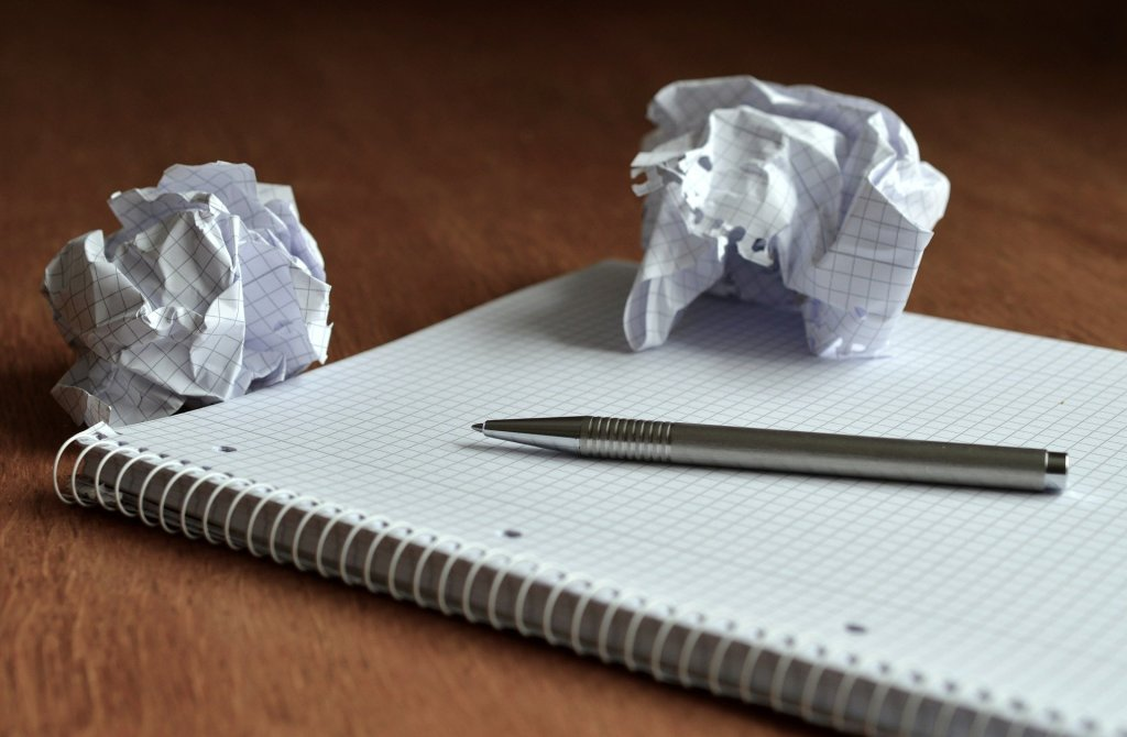 An image of a notebook with crumpled up paper on top.
